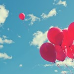 ballonnen-wegvliegen-comfortzone-ontdekken-loslaten-roze-lucht